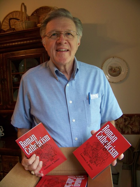 Pastor Justice holding new printing of Roman Catholicism book
